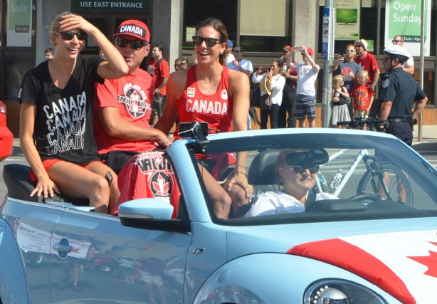 three people sitting in the back of a light blue VW convertible in a parade. They are wearing Canada T-shirts. Man in the middle with a woman on either side. Man is wearing Canada hat.
