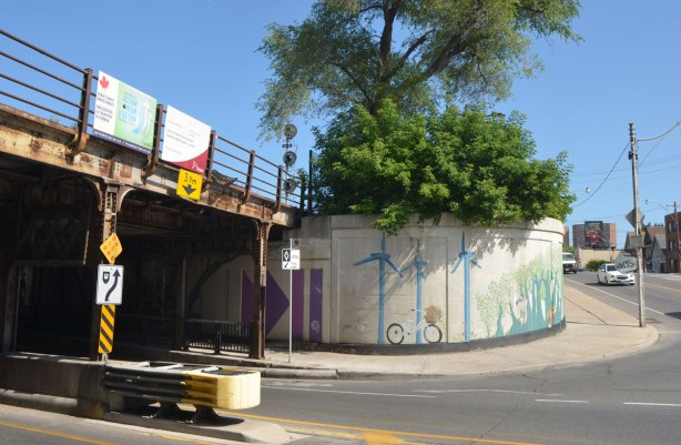 a wall of an underpass curves as it exits the railway bridge. on the curve is the continuation of a mural that was painted on the walls of the underpass. Windmills and bikes.