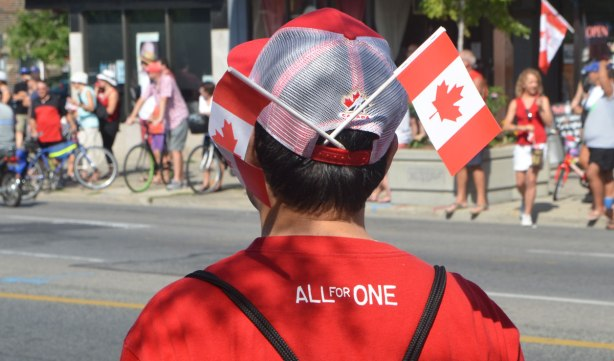 a man's back is turned to the camera, view of his head and shoulders, he's wearing a red T-shirt that has All for one written across the shoulders. He's also wearing a red baseball cap with two little Canadian flags stuck into the back of it.