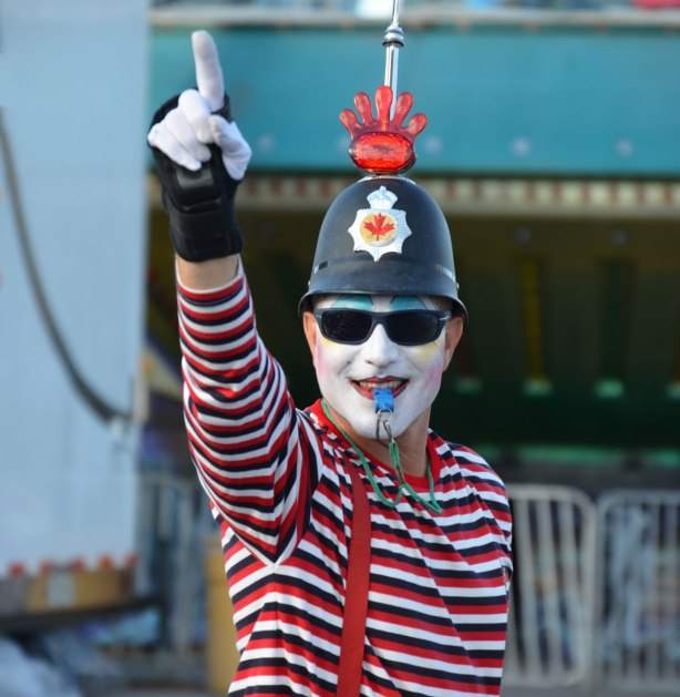 a man dressed in costume, white face, bobby hat, white gloves and a red and white striped shirt