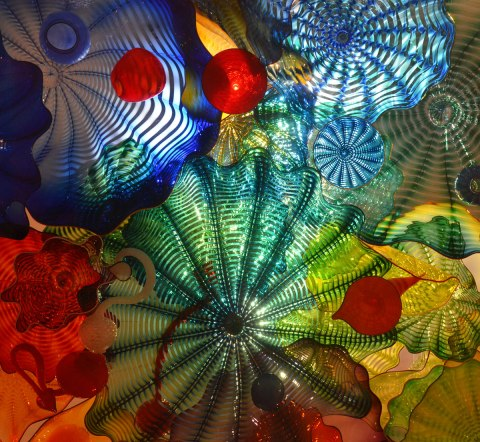 bits of coloured glass, circular shapes, ridges, back lit,