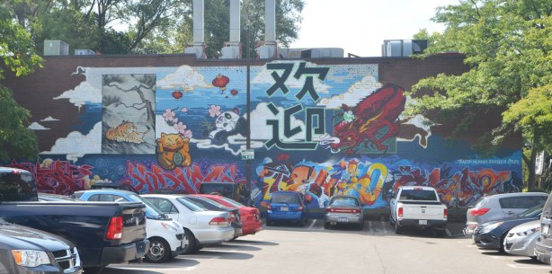 large mural across the side of a building at the back of a parking lot, Chinese characters and icons, panda bear, tiger, bamboo forest, lucky cat, chinese lantern, dragon