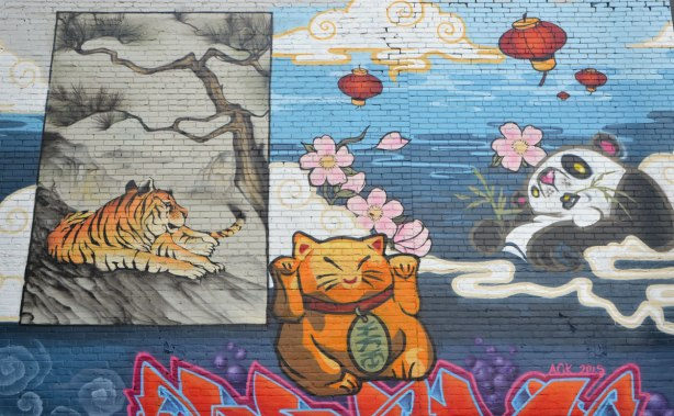 part of a mural in Chinatown East, pink cherry blossoms, red chinese lantern, panda chewing on bamboo, tiger, lucky cat