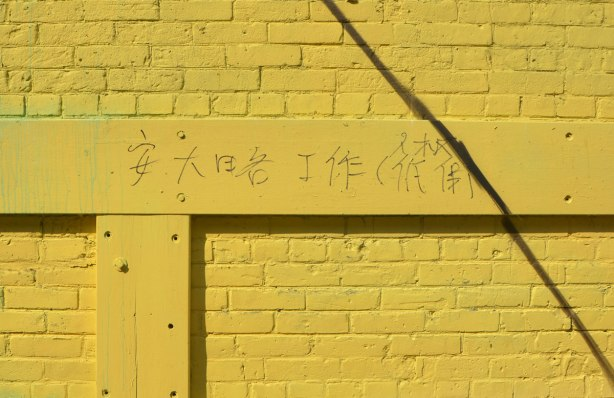 graffiti Chinese characters written on a yellow wall.