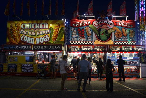 people standing in front of food vendors that ate brightly lit up, selling deep fried food such as deep fried oreos, deep fried pickles, as well as chicken and corn dogs.