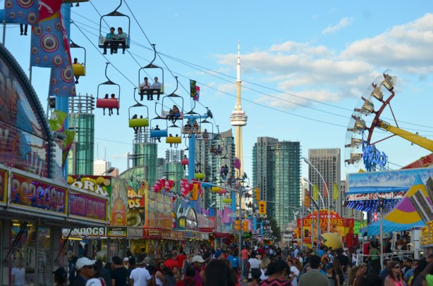 looking down the CNE midway towards the CN tower in the late afternoon as the sun gets low, riders overhead on the Skyline ride, lots of people walking, lots of signs for games and food.