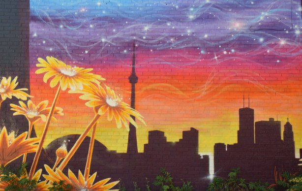 skyline of Toronto with the CN tower painted as a silhouette on a sunset sky, with some yellow flowers in the foreground of the mural.