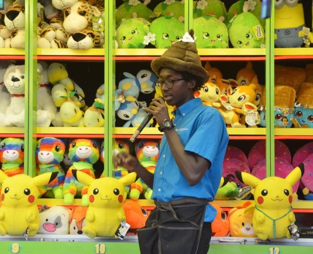 a young black man wearing a turd hat and talking into a microphone as he tries to get people interested in playing the game he's working at. A wall of stuffed prizes is behind him including yellow pokemons