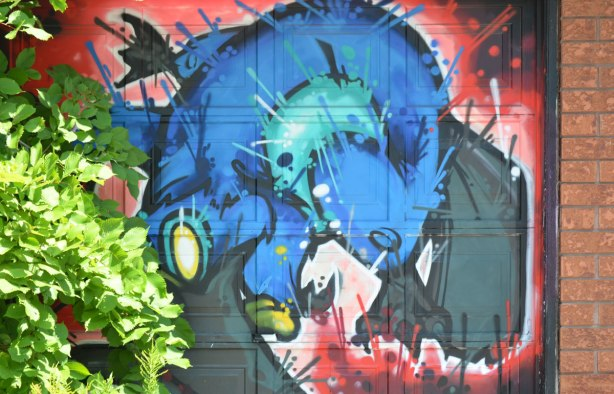 blue animal creature painted on a garage door, green shrub growing in front of part of it, art by cruz 1 in an alley