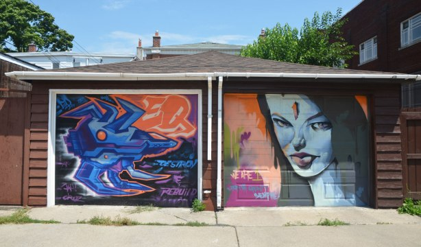 two garages in an alley with art on their doors, on the left is an abstract in blue and orange with the words destroy and rebuild. On the right is a woman's face. She's slightly blue. Words written beside her are: we are 1, mi gente siempre