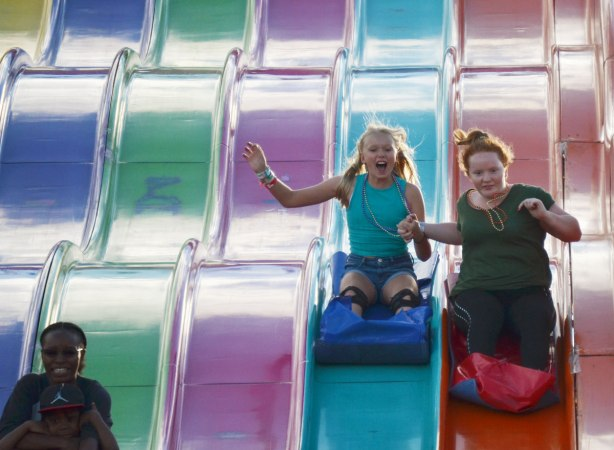 two girls coming down a large, multi lane, slide, holding hands and laughing
