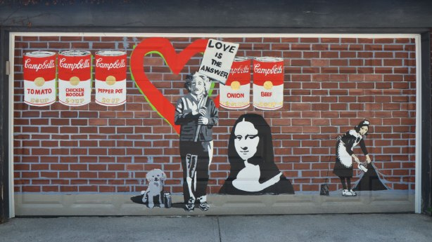 copies of famous street art painted on a garage door. Brick background has been painted on too. Mona Lisa, Campbell soup cans, the woman lifting the corner of the wall to sweep things under it. Einstein holding a placard that says love is the answer. A little dog by Albert Einstein's feet.