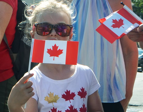 a young girl in a t shirt with yellow and red maple leafs on it, also wearing large sunglasses, holds a small Canadian flag in front of her mouth
