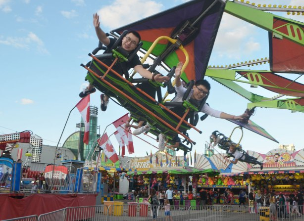 Two young Asian men on a ride, they are lying on their stomachs and appear to be flying, in circles, with the ex midway behind them