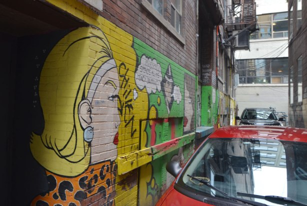 looking down one wall of an alley, a mural is painted on it, in the foreground is a woman in profile (she's looking down the lane), very yellow hair. Two cars are parked in front of the mural
