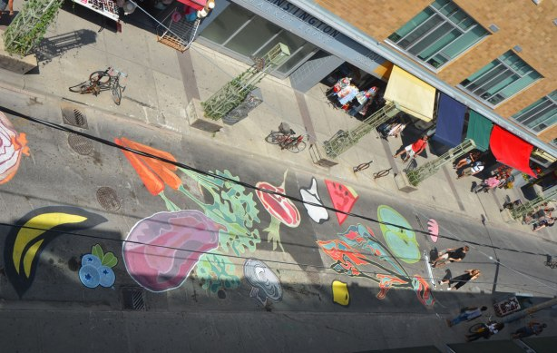 view from above of a mural on a street, fruits and vegetables, carrotes, eggplant, watermelon, beet, mushroom, lemon,