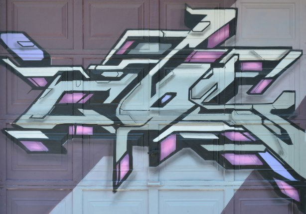 geometric street art on a garage door, pink, grey and black