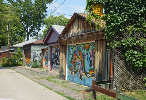 three garages in an alley, each with street art painted on their doors.