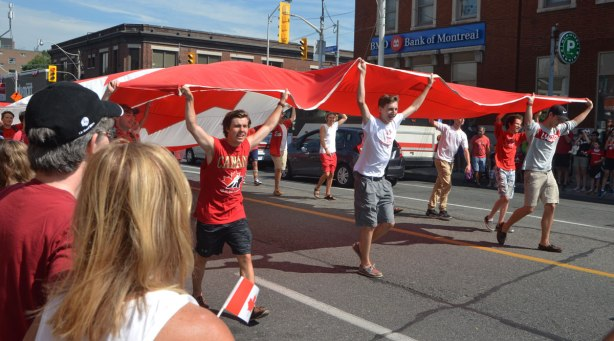 a group of young adults holding up a giant Canadian flag, lying horizontal, above their heads as they walk down the street in a parade.