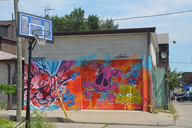 a low concrete building in an alley with street art by Cruz 1 art, one says girl power. Large pink skull, basketball hoop in the foreground.