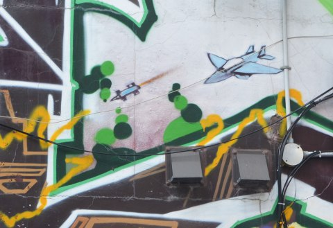 very small street art painting of a blue airplane amongst tags