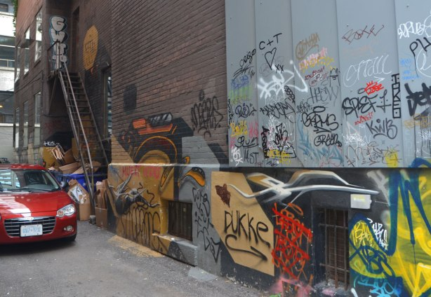 a red car is backed into an alley, and is parked there, along the wall beside the car is a lot of graffiti spray painted and written on the wall. There is a stair case in the back part of the wall.