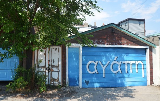garage door painted bright blue, with the Greek word for love written on it in large letters