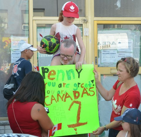 A girl sits on her father's shoulders as they show a sign that they've made to other people who have come to watch a parade. The sign says Penny you are the greatest. Canada's number 1.