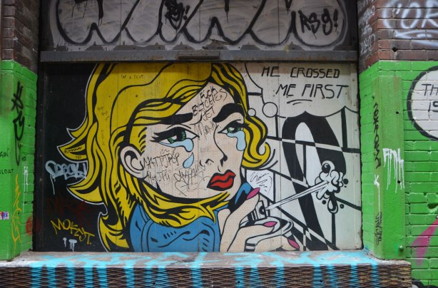 "part of a mural in an alley, a woman with bright yellow hair is spray paint out of a can with a word bubble that says ""He crossed me first"""