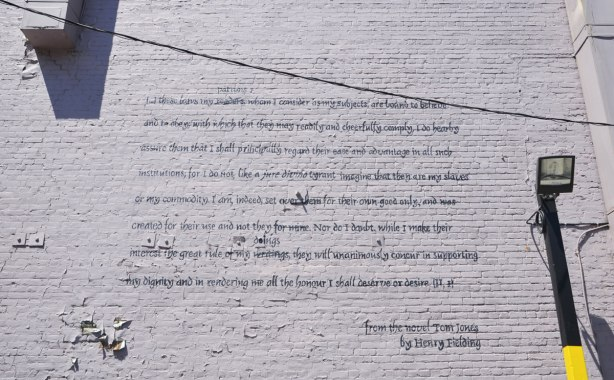 words of a quote from a novel by Henry Fielding, written in black on a lavendar coloured wall, exterior, outside