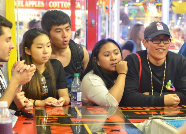 a group of young people around a counter playing a game of chance outdoors, at a fair, the cne
