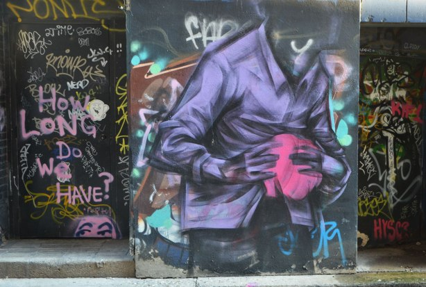 street art and graffiti in an alley, on a wall and in a doorway. On the wall is a headless man holding a pink blob in his hands, on the doorway is a lot of graffiti and tags along with the words, How long do we have?