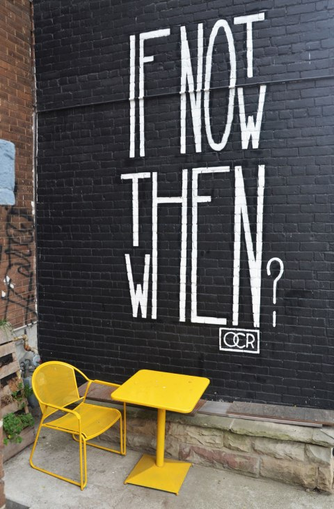 words written large in white on a black wall, if not now then when. A bright yellow table and chair sit in front of the wall.
