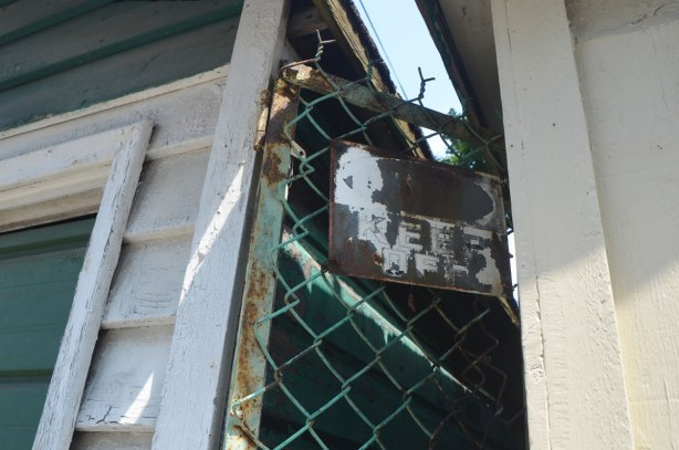 an old rusted sign that says 'keep off' attached tot he top of a chainlink fence, in between two garages in an alley