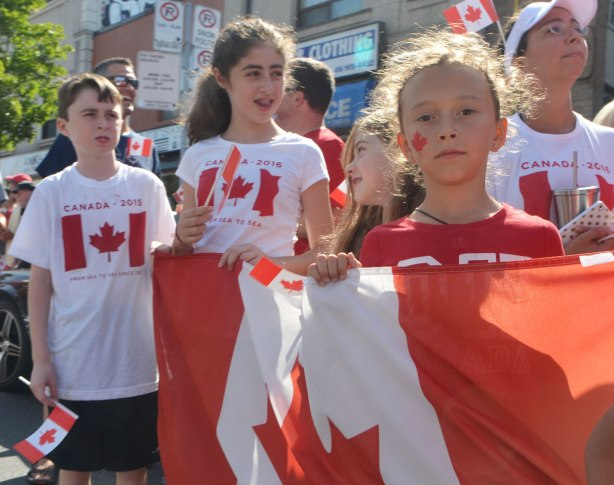 a group of kids wearing red and white Canada T-shirts with Canadian flags on them, also one girl holding a large Canadian flag, she has a little red maple leaf painted on her cheek. She is looking serious