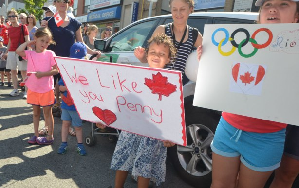 people watching a parade including a young child is holding up a red and white hand written sign that says We like you Penny. It also has a red maple leaf on it and a red heart. Another girl is holding a home made sign with the Olympics rings on it as well as a Canadian flag in a heart shape.