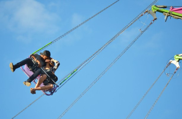 a young couple kissing on a swing that is up high