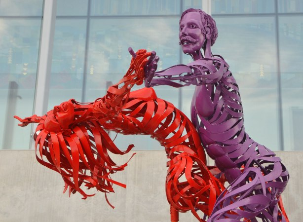 a purple male figure in metal sculpture is dancing with a woman made of red metal, she is bending backwards while he supports her.