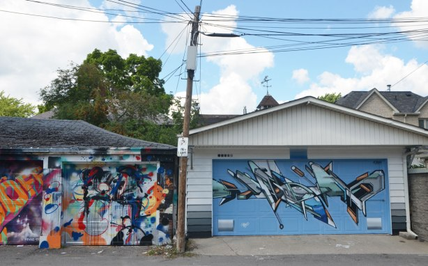 two garages in an alley, both covered in murals. On the right is a newer garage, with a weather vane on top, and a mural in blue and greys, geometric and abstract shapes. On the left is an older garage door with multicolured street art on it.
