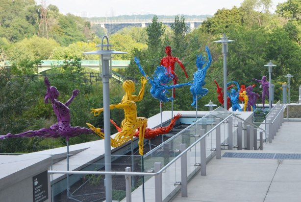 brightly coloured sculptures of figures in various active poses, made of loosely woven metal, a purple woman leaping, an orange man on his back about to catch of blue woman who is leaping head first through the air, and others as well, along the side of a building, the DVP runs beside in the background and the Bloor Viaduct bridge across the valley is in the distance