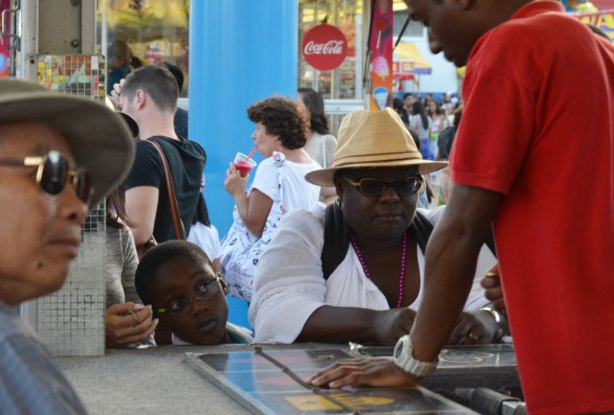 a young boy pokes his around his mother to watch her as she plays a gambling game on the midway at the Ex