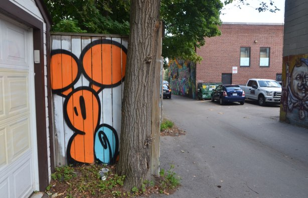 a small painting of a large orange and blue snail on a fence beside a tree in an alley