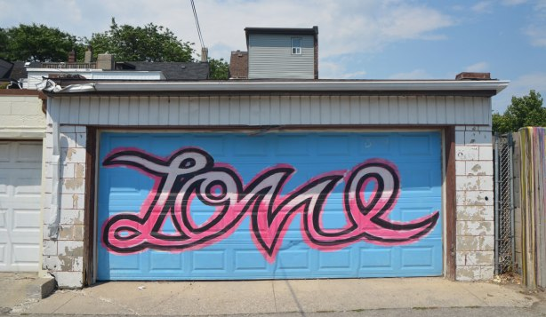 garage door painted with a large cursive lettering word love in pinks on blue