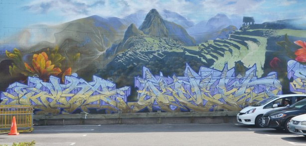 a mural with a panoramic scene of Machu Picchu, with graffiti writing signatues below.