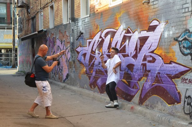 making a music video in front of the street art in an alley, a young man in white t shirt is dancing to the music (and lip synching too I think) while another man, bald, is filming him and recording him.