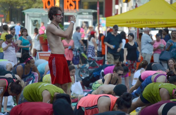 a man stands in the middle of a group taking a picture, the rest of the group is on the ground, on their yoga mats, doing yoga at a yogathon, outdoors,