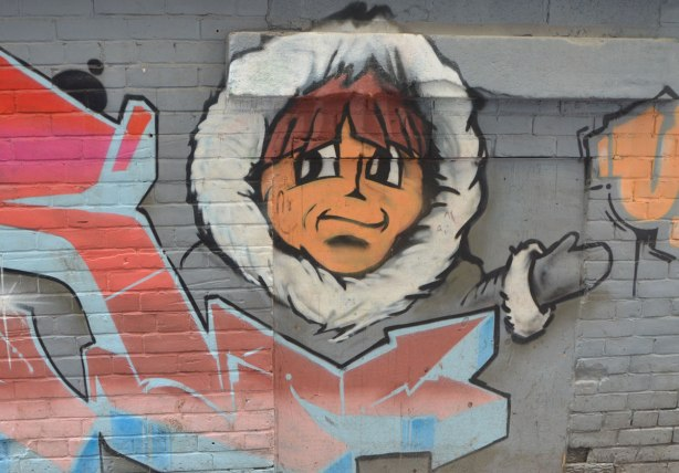 street art on a grey brick wall, head of a young man in a fur lined hood of a parka
