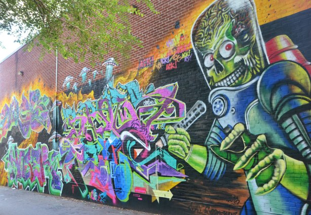 large mural on a two storey brick building, mural is called Mars Attacks, shows a green robot like alien and lots of tags.
