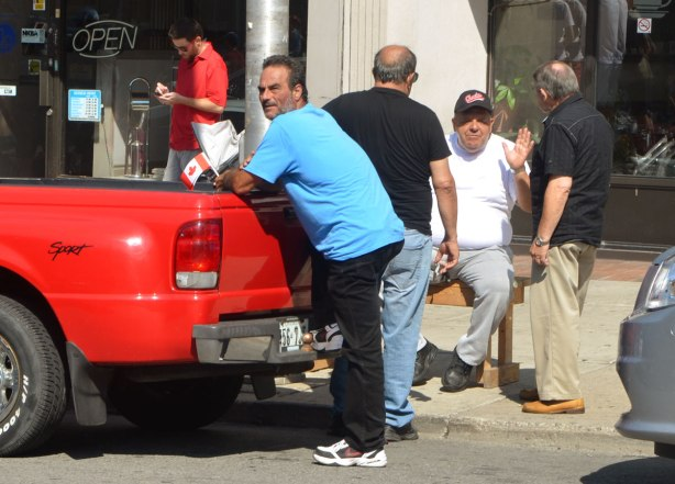 a middle age man leans against the back of a pickup truck that is parked beside a sidewalk where three older men are talking. One of them is sitting on a bench and facing the camera.