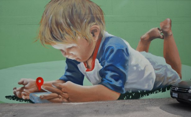 mural of a boy lying on his stomace, with his feet in the air. He islooking at an electronic device